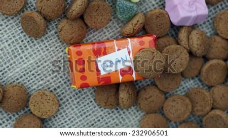 Presents with names between Dutch Pepernoten , typical Dutch treat for Sinterklaas on 5 december - stock photo