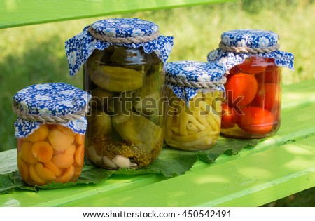 Preserved asparagus beans, apricots, cucumbers, tomatoes in glass jars  on green wooden background with leaf - stock photo