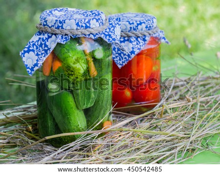 Preserved cucumbers and tomatoes in glass jars  on hay background - stock photo