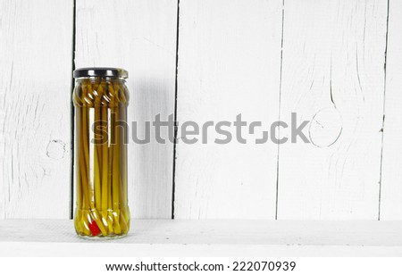 Preserved food in glass jar, on a wooden shelf. Marinaded a ramson - stock photo