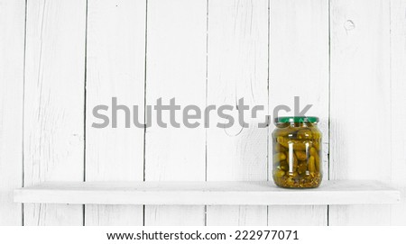 Preserved food in glass jar, on a wooden shelf. Marinaded gherkins - stock photo