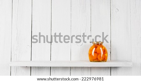 Preserved food in glass jar, on a wooden shelf. Marinaded peaches - stock photo
