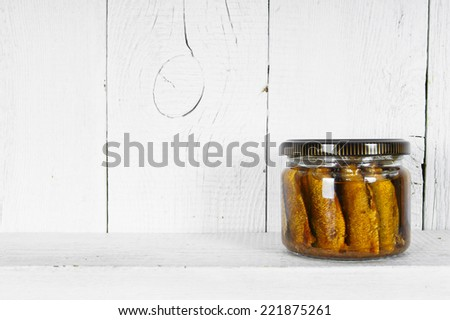 Preserved food in glass jar, on a wooden shelf. Marinaded sprats - stock photo
