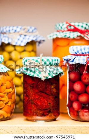 Preserved fruits and vegetables on the wooden shelf. - stock photo