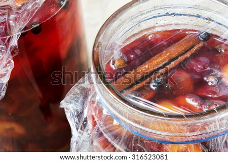 preserved red fruits with spices in glass jars, homemade Christmas gifts - stock photo