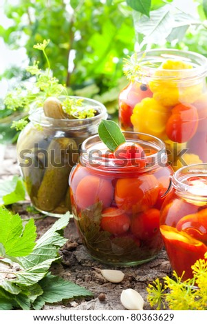 preserved tomatoes,cucumbers,peppers and patisson in jars - stock photo