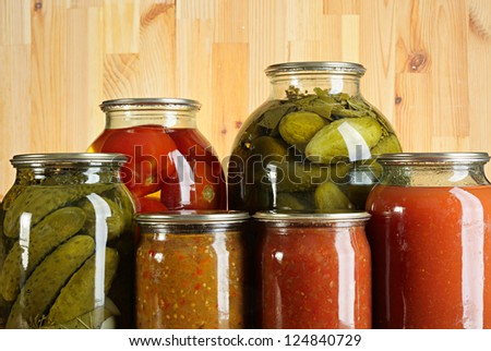 Preserved vegetables, ketchup and salads in glass jars