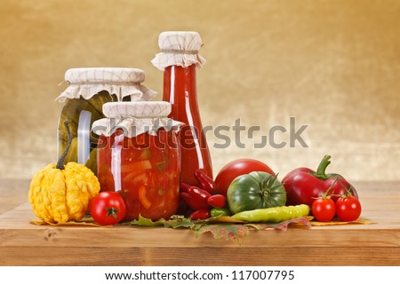 Preserves and fresh vegetables on wooden board - stock photo