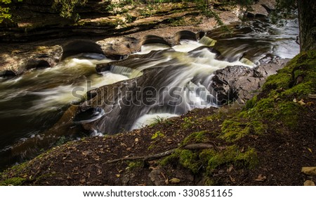 Presque Isle Waterfalls. The Porcupine Mountains are the largest state park in Michigan. The park offers hiking, camping, scenery and a multitude of waterfalls along the Presque Isle River. - stock photo