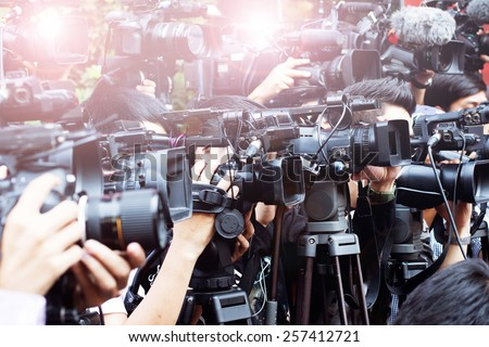 press and media camera ,video photographer on duty in public news coverage event for reporter and mass media communication - stock photo