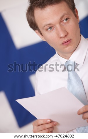 press conference speaker in front of a finnish flag - stock photo