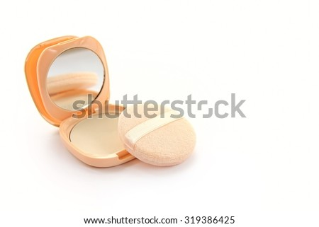 Pressed powder and powder puff on white background.