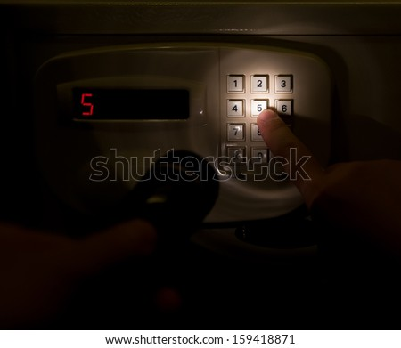 pressing a safebox in a dark space - stock photo