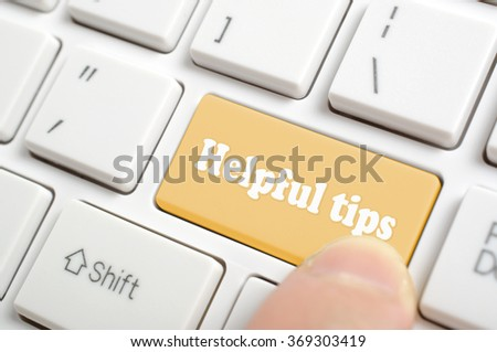Pressing brown helpful tips key on keyboard - stock photo