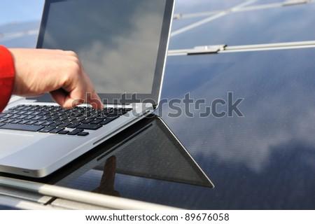 Pressing enter button on laptop at  photovoltaic solar panels - stock photo
