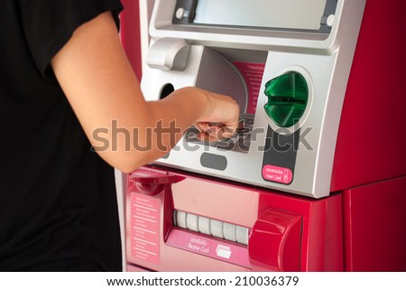 pressing password number on ATM machine - stock photo