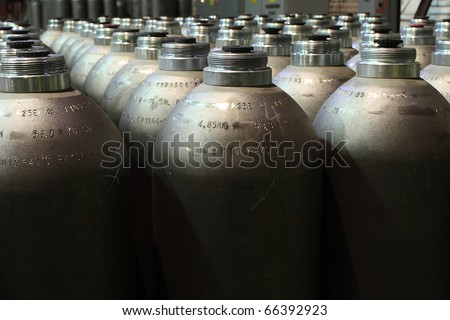 pressure cylinders standing in the machinery waiting to be filled in - stock photo