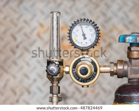 Pressure gage and valves of gas argon on the steel wall background.