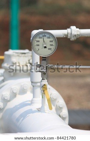 pressure gauge top of the white aboveground pipe. - stock photo