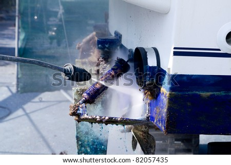 pressure washer cleaning boat hull barnacles antifouling and seaweed - stock photo