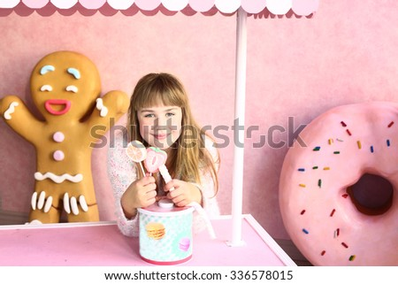 preteen blond girl in confectionery world with ginger man and donut on the background - stock photo
