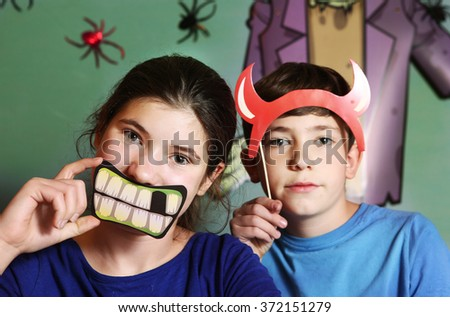 preteen boy and teenage girl brother and sister prepare for halloween party with spooky requisites and spider and frankenstein on the background - stock photo