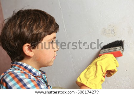 preteen boy help wallpapering, boy with brush apply glue on the wall
