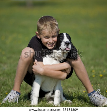 Preteen boy poses in a grass field with his Springer Spaniel puppy. - stock photo