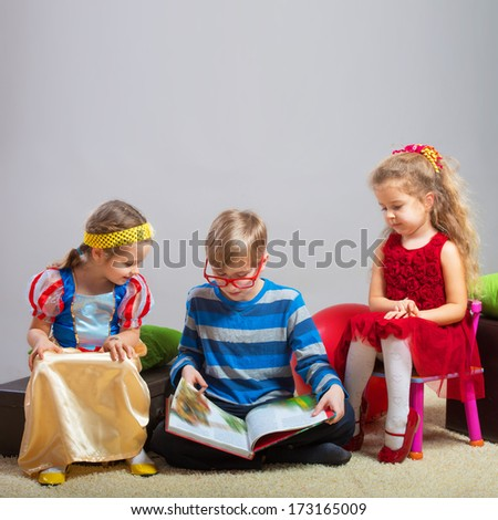 Preteen boy reading a fairy tale to two little girls - stock photo