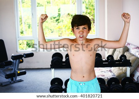 preteen boy training with dumbbells in gym - stock photo