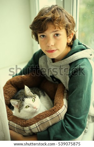preteen boy with cat in pet bed close up photo