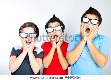 Preteen boys having fun, wearing 3D movie glasses and watching cinema, crazy facial expression, surprised kids, portrait of a screaming teens, children with open mouths - stock photo