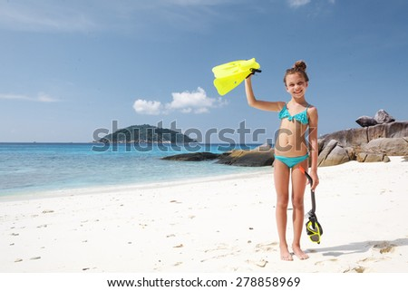 Preteen child posing with snorkeling equipment on a tropical beach - stock photo