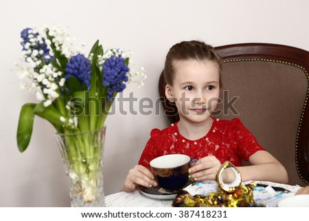 preteen girl in red dress drink tea close up portrait with hyacinth flowers bouquet in vase - stock photo