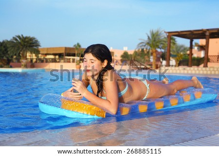 preteen girl in swimming suit with inflatable matrass drink cocktail on the blue pool water and palms background - stock photo