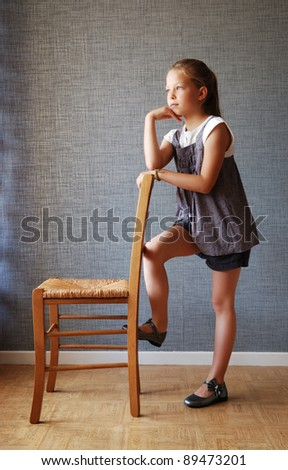 Preteen girl is standing near the chair. She leans on the chair and looks sideways dreamily. - stock photo