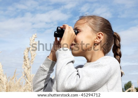 Preteen girl looking at far with binoculars outdoors - stock photo