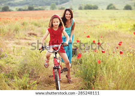 Preteen girl on bicycle with mother in spring field - stock photo