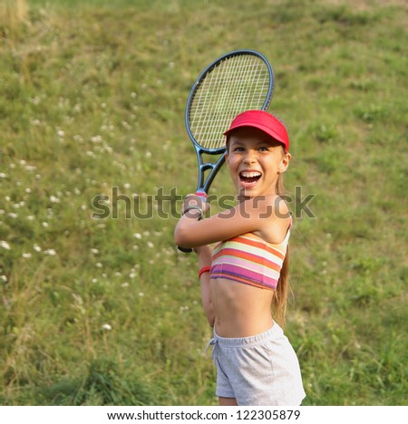 Preteen girl playing tennis on grass background - stock photo