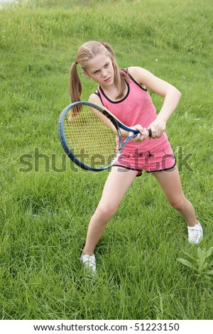 Preteen girl playing tennis outdoors on green grass background