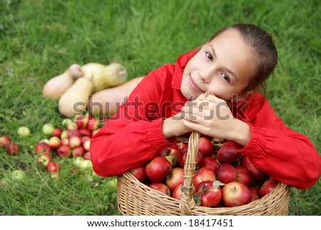 Preteen girl sits in green grass holding basket of organic apples - stock photo
