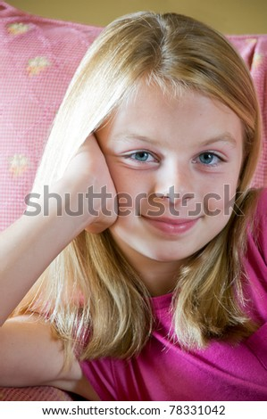 Preteen girl sitting in chair before window with pleasant smile and magenta tone surroundings - stock photo