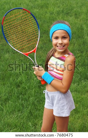 Preteen girl with tennis racket on grass background - stock photo