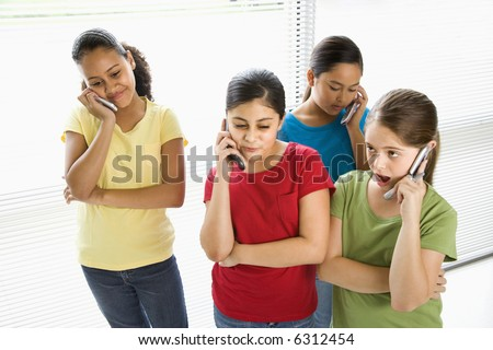 Preteen girls of mutiple ethnicities talking on cell phones.