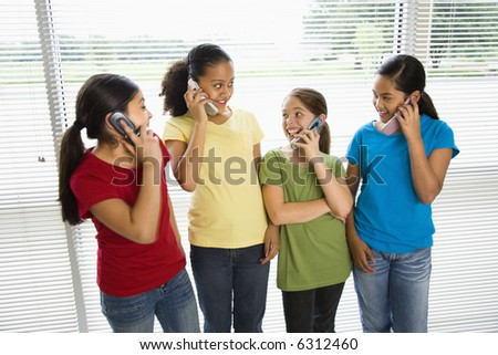 Preteen girls of mutiple ethnicities talking on cell phones. - stock photo