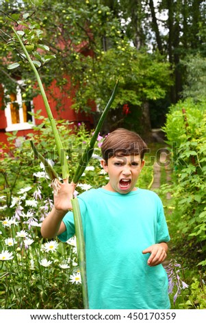 preteen handsome boy acting monster with long onion clows grimacing on the summer garden background