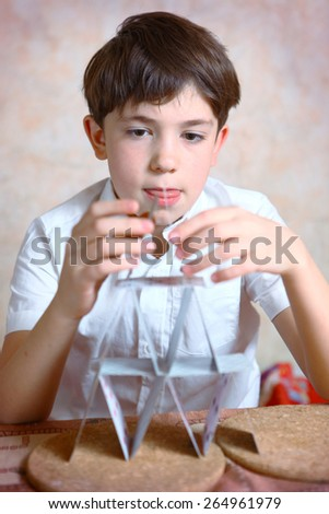 preteen handsome boy build card house - stock photo