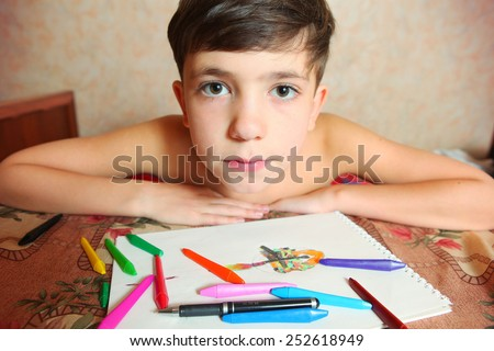 preteen handsome boy drawing with colored pencils and crayons - stock photo