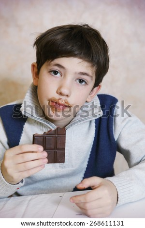 preteen handsome boy eat cho?olate bar with dirty mouth - stock photo