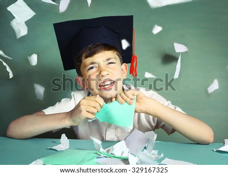 preteen handsome boy in graduation cap  tear his copybook for pieces - stock photo